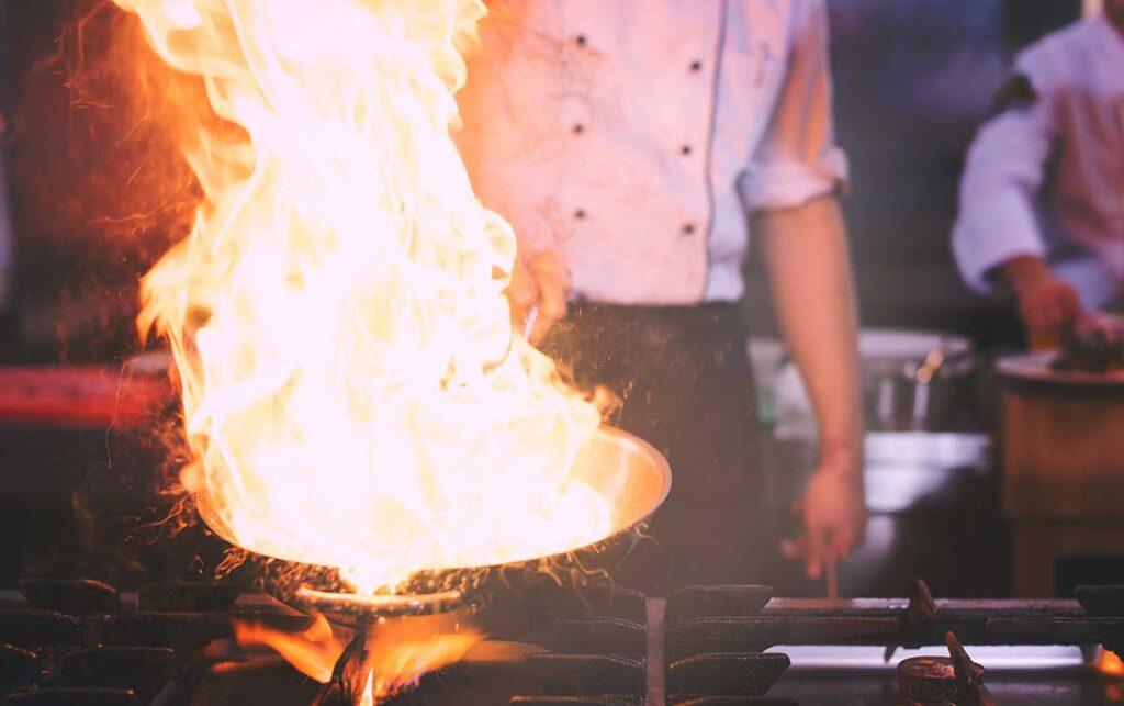 pentola in cottura con fiamma e cuoco