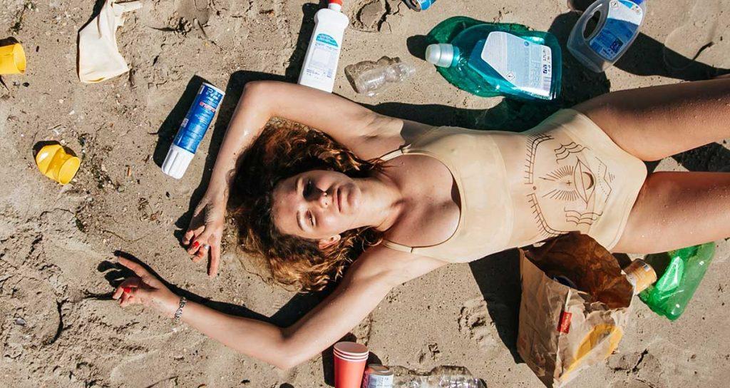 donna stesa su una spiaggia sporca di plastica
