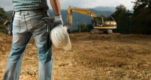operai con caschetto e cantiere